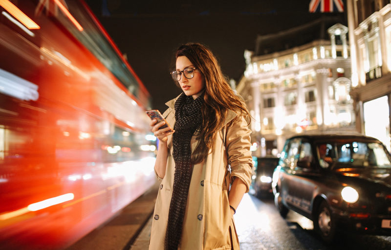Women in the streets of the UK on her mobile device