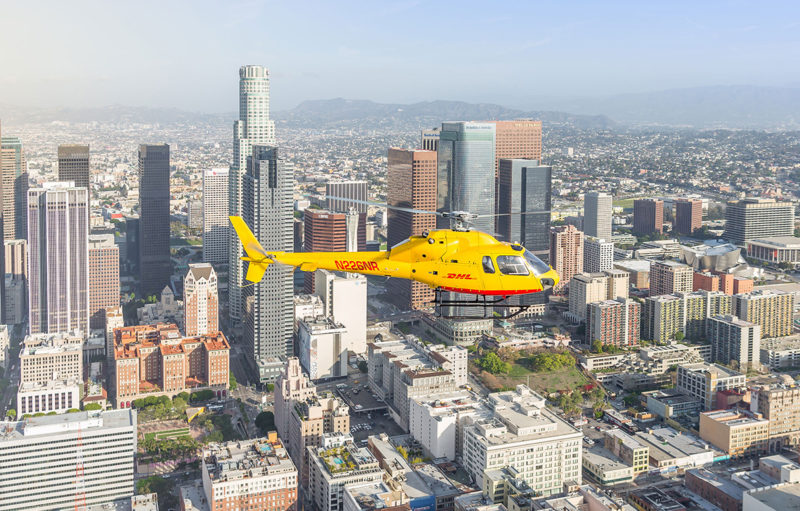 DHL helicopter flying over a city
