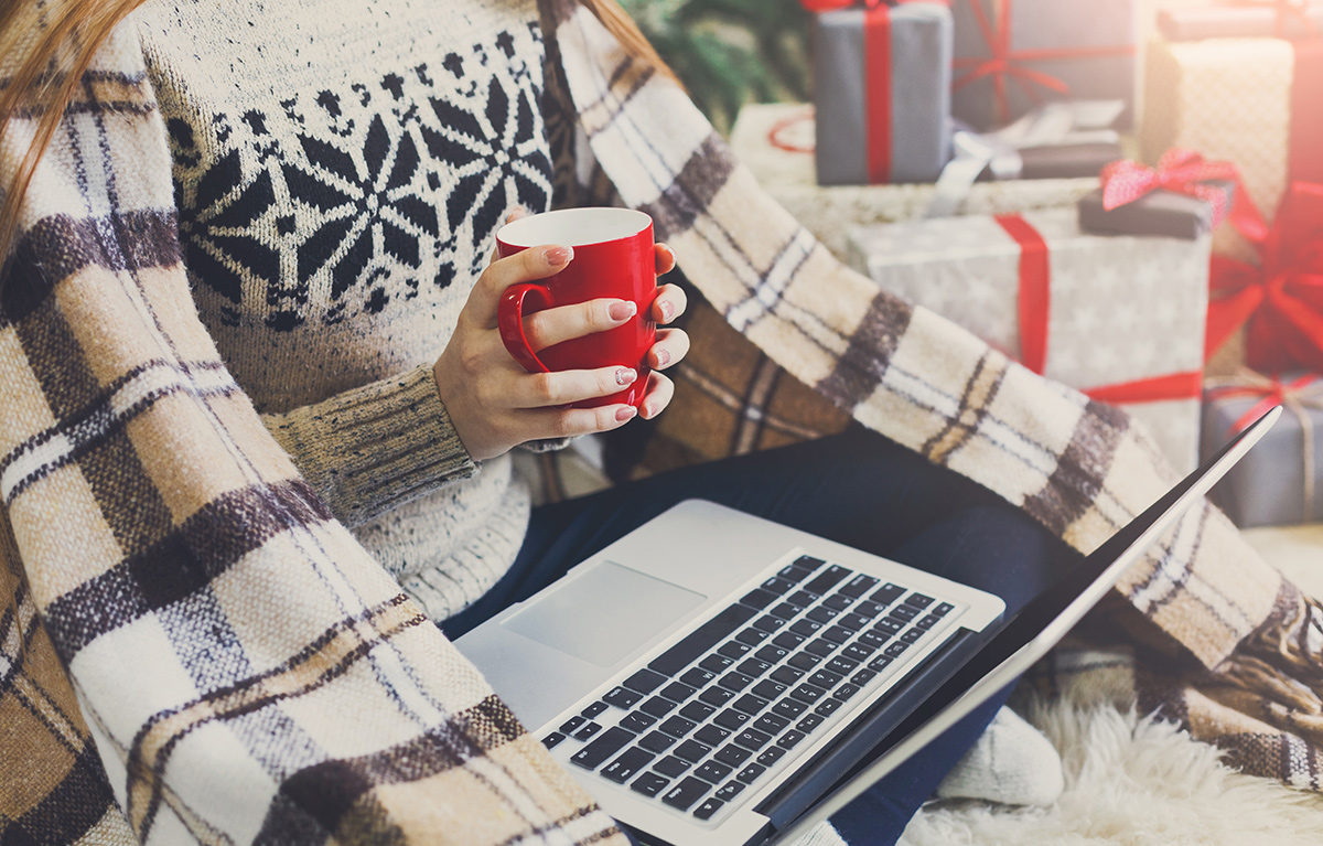 Women sitting around holiday gifts while holding a cup and her laptop is on her lap