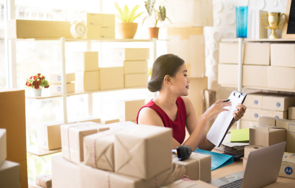 Small business asian woman owner working from her home office with boxes around her, she is looking at an order chart and sitting in front of her laptop