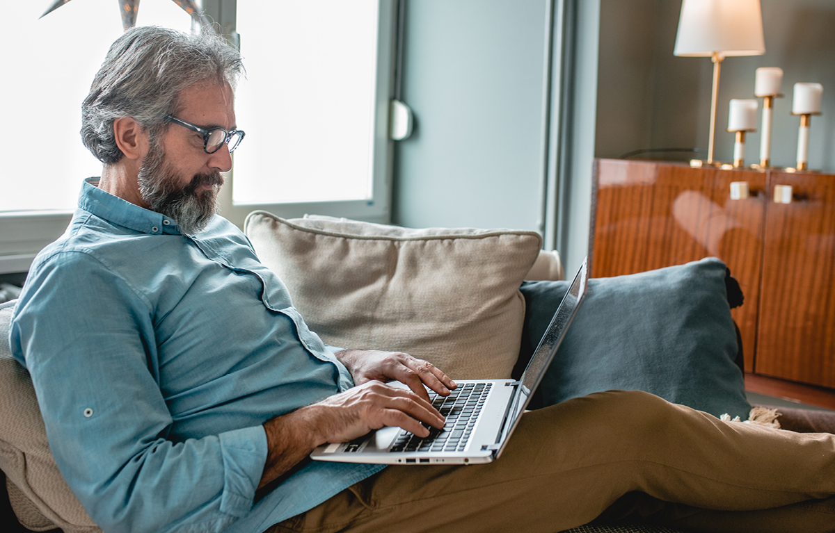 Older male sitting on his couch, he's holding a laptop on his lap and using the keyboard