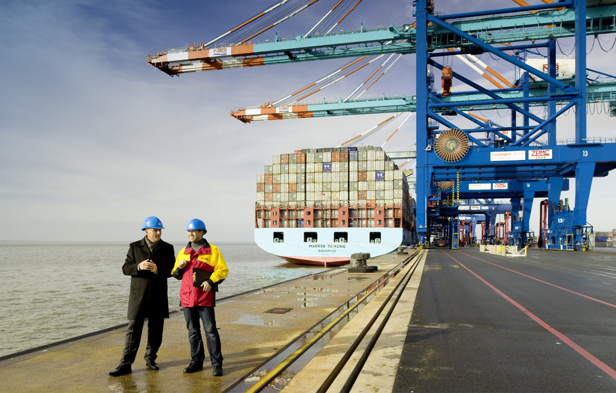 Two men wearing hard hats and standing in front of a container ship