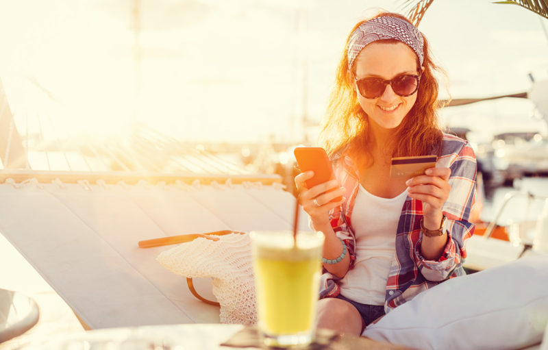 Woman on a hammock using her credit card and phone for online shopping