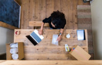 Woman working on her laptop and packing up an order on a wooden table