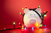 In front of a red background, there's a ceramic pig with holiday lights wrapped around it