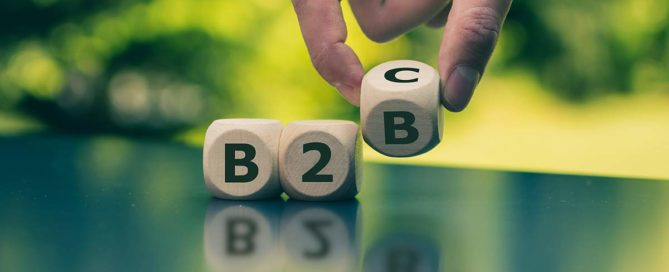 Closeup of three dices that spell B2B, the last dice show the letter B and C, a hand is holding the last dice