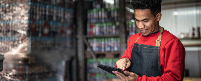 Man wearing a red sweatshirt and a jean apron, he is in a warehouse on a tablet