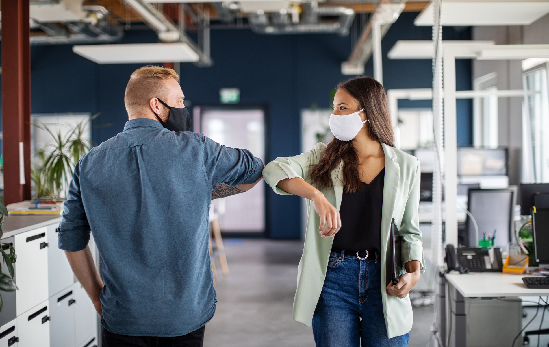 Colleagues greeting each other with masks on.
