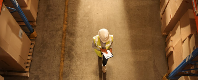 Worker looking at a tablet with a construction hat.